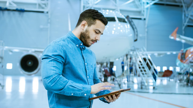 In Big Company Hangar Aircraft Maintenance Engineer Uses Tablet Computer while Standing Near Big New Shiny White Plane.