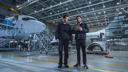 Team of Aircraft Maintenance Mechanics Moving through Hangar. Holding Tablet Computer