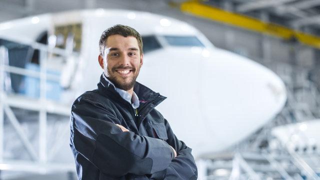 Portrait of Aircraft Maintenance Mechanic in Hangar. Airplane on Background.