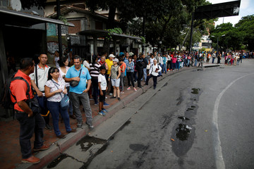 People queue as they wait for transportation in Caracas