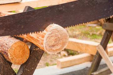 Hand saw cutting log close up