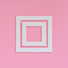 Empty white frames on a pink textured paper background, top view. Flat lay