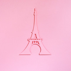 Cut from the paper Eiffel Tower on a pink textured background, top view. Flat lay