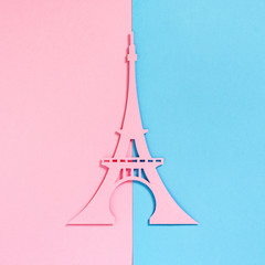 Cut from the pink paper Eiffel Tower on a pink and turquoise textured background, top view. Flat lay