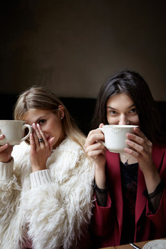 Two girls drinking coffee and have a fun in cafe while having a good time together.Concept frienship.Girlfreind.Red jacket and white fur.Blonde and brunette