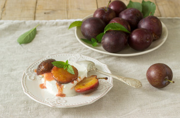 Ice cream with caramelized plums and ripe plums on a wooden background. Rustic style.
