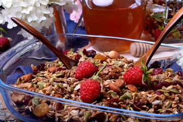 Granola made of oatmeal flakes, nuts and seeds decorated with fresh raspberries