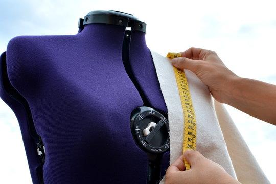 Mujer trabajando tomando medidas con una cinta métrica sobre un trozo de tela colocado en un maniquí de modista realizando un diseño de moda