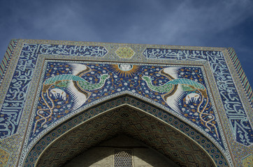 The facade of Nadir Divan-Beghi madrasah is decorated with multicolored majolica with a predominance of blue tones, Bukhara, Uzbekistan.