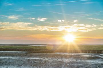 wunderschönes, farbenprächtiges Watttenmeer der Nordsee bei Suedwesthoern zum Sonnenuntergang