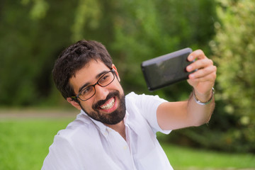 Happy Young man taking a selfie in the park