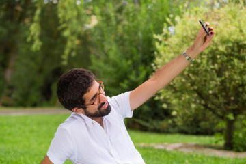 Young hipster man taking a selfie in the park