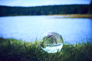 Glass ball display lake and forrest. The concept of environment, nature protection, ecology. Selective focus
