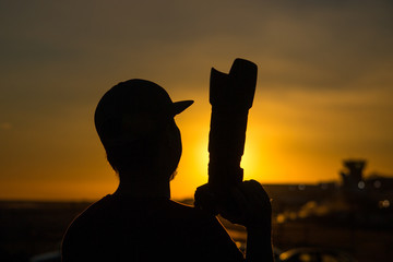 silhouette of a photographer in a sunset
