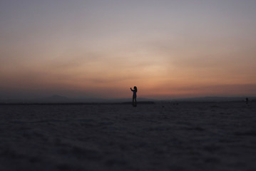 A woman is silhouetted during the sunset at a salt lake in Larnaca