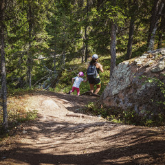 Mother and daughter run and have fun on a hiking trail in the woods. Sunny green forest. Skule mountain, high coast in northern Sweden.