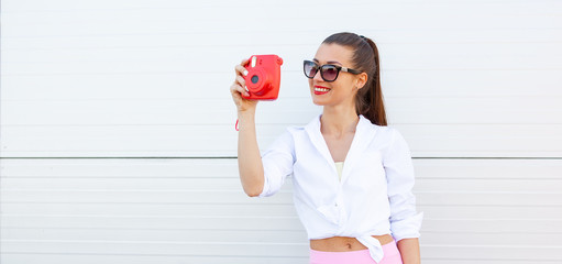 Fashion portrait of pretty smiling woman in sunglasses making photo by the camera against the grey wall. Wireless Headphones, fitness bracelet on the hand