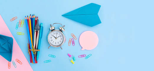 Back to school styled flat lay scene with multicolored school supplies with paper plane on pink and blue background banner