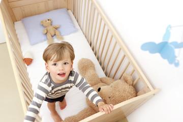 Ein zweijähriger Junge steht in seinem Kinderbett