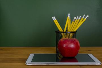 Tableta digital y manzana en el escritorio frente a la pizarra