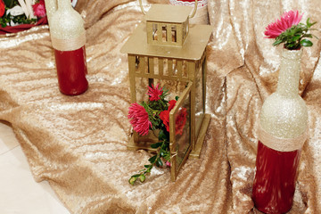 stylish decorated golden bottles of wine with red flowers and lanterns, luxury rustic decor for wedding ceremony and reception