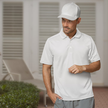 A handsome man stands in the patio looking over to his right with a white baseball cap and white golf shirt.