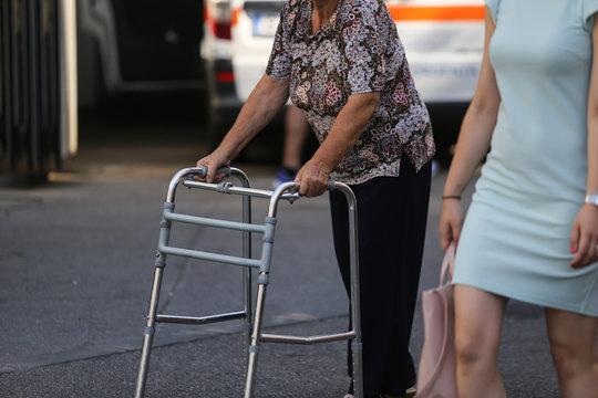 Elderly woman using a metal walker
