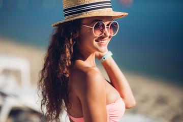 Laughing freedom woman in summer straw hat posing beside exotic summer beach hot summer fashion accessory,stylish sunglasses,bikini.Sexy perfect fit body woman.