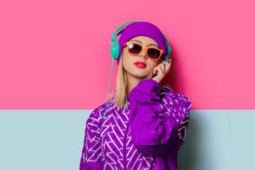 Young blonde girl in 90s sports jacket and hat on pink and blue background.