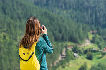 Woman tourist with a backpack and camera taking pictures outdoors on a summer day