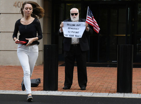 After a guilty verdict on the first count, an unidentified man holds a sign while a reporter runs out of the U.S. District Courthouse for the fourth day of jury deliberations in former Trump campaign manager Paul Manafort's trial