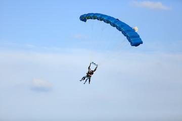 Dwóch mężczyzn szybuje w duecie na spadochronie.