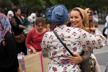 Muslim women greet each other after Eid al-Adha prayers in Washington Square Park in New York City