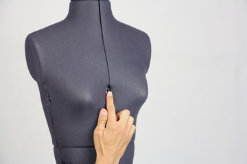 tailor hand gently change the size of the breast on a female sewing mannequin, gray background, copy space