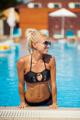 Beautiful blonde woman posing near swiming pool
