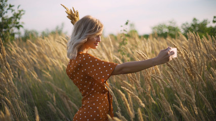 attractive fun hippie blonde woman in the field at sunset making a selfie with a bouquet
