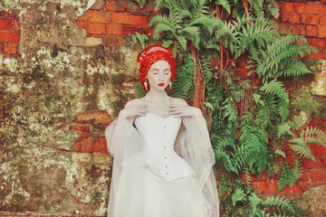 Fairytale hero. Renaissance redhead princess with hairstyle in castle. Fabulous rococo duchess in white dress against the backdrop of old fern wall. Duchess in corset. Fairytale princess in palace Wall mural