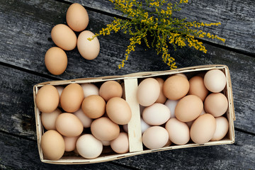 Chicken eggs in basket on rustic wooden background.