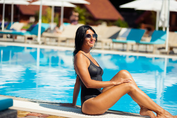 Beautiful girl in black swimwear near the pool