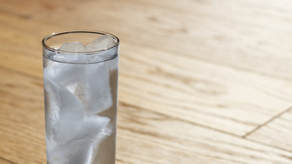 Glass with water and ice with wooden floor in the background