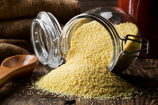 Heap of raw, uncooked couscous in glass jar on wooden table