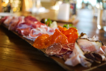Assortment of colorful, tasty and delicious Italian antipasto. Prosciutto di Parma or Parma and Chorizo sausage and Salami and Pancetta on a wooden board. Soft Focus. Natural light.