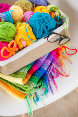 Basket with colored, bright yarn for knitting on a white armchair. Crochet.
