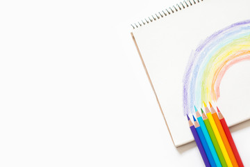 Many bright colored pencils. Rainbow painted on white background.