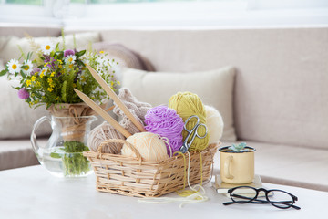 Wool and cotton yarn in a wicker basket on a white table in a light interior. A bouquet of wild flowers.