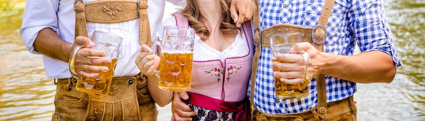 Oktoberfest Freunde in Lederhosen und Dirndl trinken Bier an der Isar
