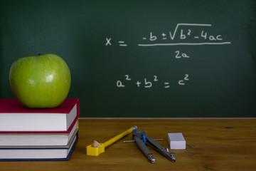 Back To School, una manzana verde sobre una pila de libros frente a una pizarra