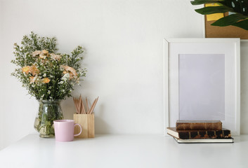 Stylish workspace with poster, book and flower bouquet. Workplace desk and copy space.