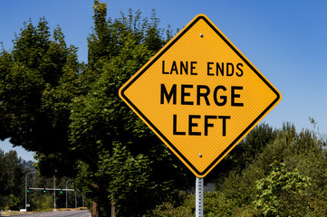 Lane ends merge left sign with trees