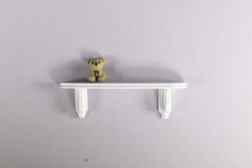 White wooden bookshelf against a cream wall with a teddy bear sitting on shelf.
